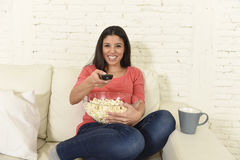 Happy woman eating popcorn watching television at sofa couch happy excited enjoying movie Royalty Free Stock Images