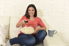 Happy woman eating popcorn watching television at sofa couch happy excited enjoying movie Stock Photos