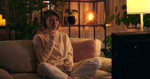 Woman eating popcorn and watching tv at night