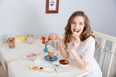 Happy woman eating small cakes and drinking latte in cafe Royalty Free Stock Photo