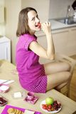 Happy woman eating strawberry for breakfast Royalty Free Stock Photos
