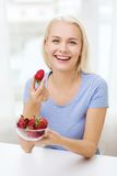 Happy woman eating strawberry at home Stock Photos