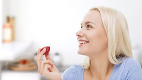 Happy woman eating strawberry on kitchen Royalty Free Stock Image
