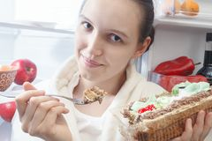 Woman near refrigerator. Happy woman eating sweet cake near refrigerator looking at camera Stock Photography