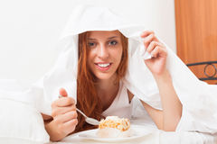 Happy woman eating sweet cake under  sheet Stock Photo