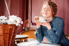 Happy woman eating sweet tasty cupcake in outdoor cafe Royalty Free Stock Photos