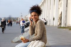 Happy woman eating and talking on cell phone Stock Photography