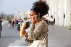 Happy woman eating and talking on mobile phone Royalty Free Stock Image