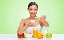 Happy woman eating yogurt for breakfast Stock Photos