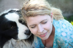 Happy woman embracing her loving and cute dog Royalty Free Stock Image