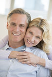 Happy Woman Embracing Man From Behind At Home Stock Photography