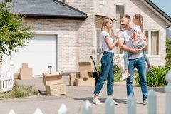 Happy woman embracing smiling husband while he holding daughter inf front of. New house stock image