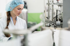 Happy woman employee working as manufacturing engineer in factor. Happy female employee wearing protective headwear and white lab coat while working as a stock photos