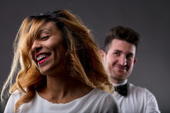 Happy woman with endorsing man blurred in background. Laughter of a happy women with his men happily looking to her because he loves her and agrees with her royalty free stock image
