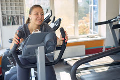 Happy woman is engaged on a stationary bike Royalty Free Stock Photos
