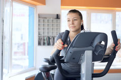 Happy woman is engaged on a stationary bike Stock Photos