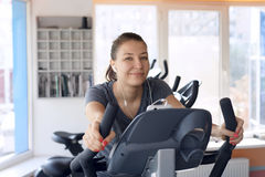 Happy woman is engaged on a stationary bike Royalty Free Stock Photo