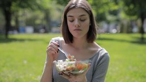 Happy woman enjoy eating fresh salad sitting at summer park. Happy woman enjoy to eating fresh salad sitting at summer park, healthy food concept stock footage