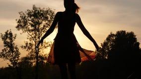 Happy woman enjoy life dancing and turning around. Sunset sunlight shine through light transparent dress stock video