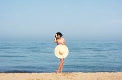 Happy woman enjoying beach relaxing joyful in summer by blue water. stock photography