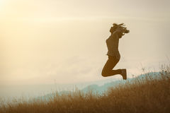 Girl jumping on mountain and having fun on idyllic field at suns Stock Image