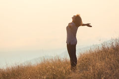 Young woman standing on mountain and having fun on grass field Stock Photos