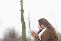 Happy woman enjoying cup of hot beverage in winter outdoors Royalty Free Stock Images