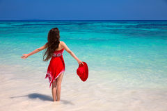 Happy woman enjoying on exotic beach in summer by tropical blue. Water. Attractive girl in red dress resting, outdoor portrait. Bliss freedom concept. Travel Royalty Free Stock Image