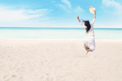 Happy woman enjoying freedom. Free woman enjoying freedom by jumping on the tropical beach. Shot at beautiful beach in maldives Stock Photography