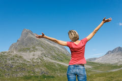Happy woman enjoying freedom. Back view of happy woman enjoying freedom with arms outspread enjoying peace, serenity in nature outdoors, in top of mountains Stock Photo