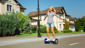 Happy woman enjoying freedom while riding hoverboard. Sense of freedom. Inspired happy woman riding a hoverboard down the street and spreading hands, enjoying Royalty Free Stock Images