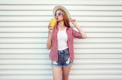 Happy woman enjoying fresh orange juice in summer round straw hat, checkered shirt, shorts on white wall royalty free stock images