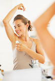 Happy woman enjoying freshness after applying roller deodorant Royalty Free Stock Images