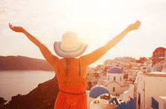 Happy woman enjoying her holidays on Santorini, Greece. Happy woman in sun hat enjoying her holidays on Santorini, Greece. View on Caldera and Aegean sea from stock photos