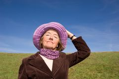 Happy woman enjoying life :). Mature and cheerful, joyful and happy woman enjoying life on a meadow, having fun with her violet hat - presenting good condition royalty free stock photos