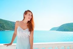 Happy woman enjoying luxury resort on sea. Beautiful woman in dress standing on balcony in bright sunshine on background of tropical sea bay and blue water stock photography