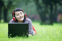 Happy woman enjoying music. A happy woman relaxing at the park while enjoying music using her headphone Royalty Free Stock Photos