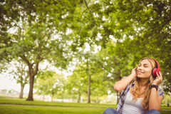 Happy woman enjoying music with eyes closed at park Stock Photo