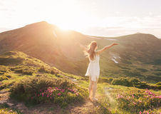 Happy woman enjoying the nature in the mountains. And looking on sky with raised hands. Freedom concept Royalty Free Stock Images