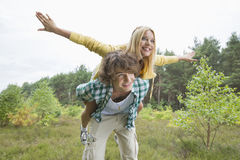 Happy woman enjoying piggyback ride on man in forest Stock Image