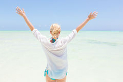 Happy woman enjoying, relaxing joyfully in summer on tropical beach. Royalty Free Stock Photography