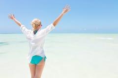 Happy woman enjoying, relaxing joyfully in summer on tropical beach. Stock Photo