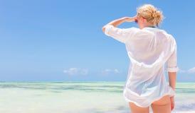 Happy woman enjoying, relaxing joyfully in summer on tropical beach. Stock Image
