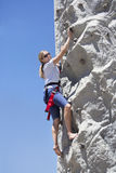 Happy woman enjoying rock climbing while on vacation royalty free stock image