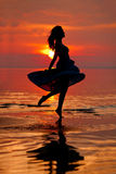 Happy Woman enjoying in Sea Sunset. Silhouetted against the suns Royalty Free Stock Photo