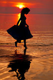 Happy Woman enjoying in Sea Sunset. Silhouetted against the suns Royalty Free Stock Image