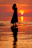 Happy Woman enjoying in Sea Sunset. Silhouetted against the suns stock photo