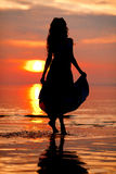 Happy Woman enjoying in Sea Sunset. Silhouetted against the suns Royalty Free Stock Images