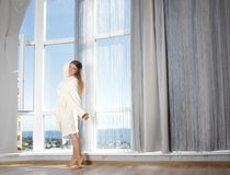 Happy woman enjoying sea view in hotel / room Stock Photo