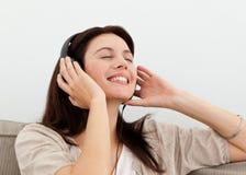 Happy woman enjoying a song on the sofa Stock Photo